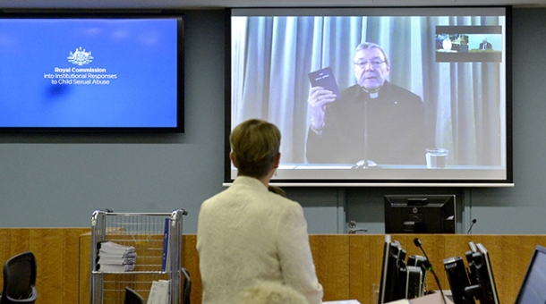 Cardinal George Pell appears before the Commission via videolink holding a bible
